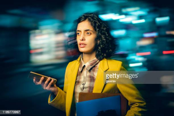 young adult businesswoman returns from her office and rushes on a busy road. - differential focus stock pictures, royalty-free photos & images