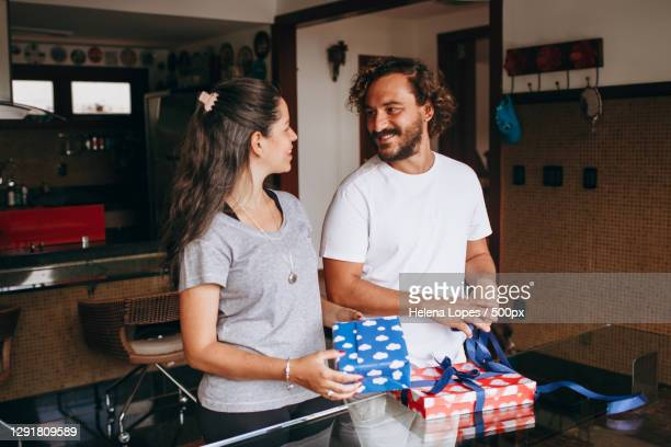 young adult caucasian couple wrapping christmas holiday gifts together at home in kitchen,belo horizonte,state of minas gerais,brazil - helena price stock-fotos und bilder