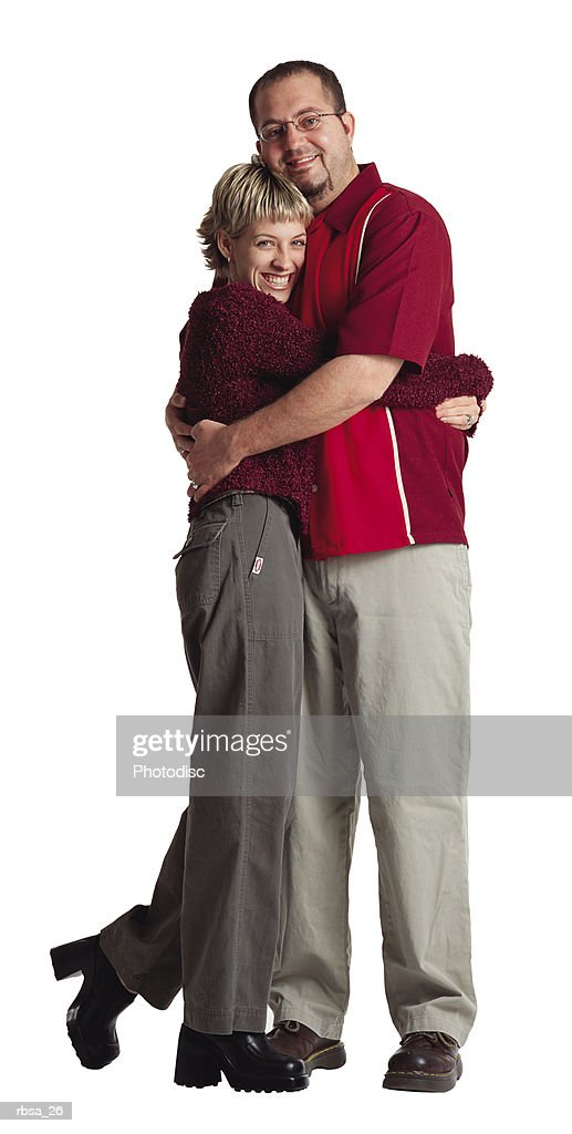 young adult caucasian male glasses and female wear red shirts and khakis embrace smiling at camera : Foto de stock