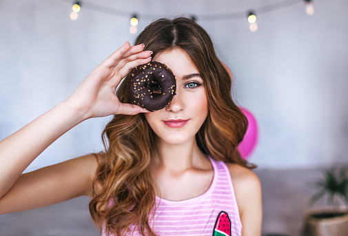 young adult caucasian woman with a chocolate donut, sugar consumption, beautiful teenage girl looking through donut, sweet, diet, unhealthy food, junk food, youth culture - gettyimageskorea