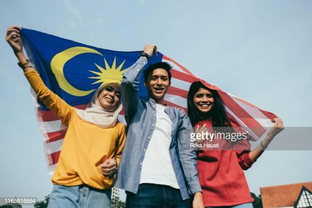 joven adulto celebrando el día de la independencia de malasia - malasia fotografías e imágenes de stock