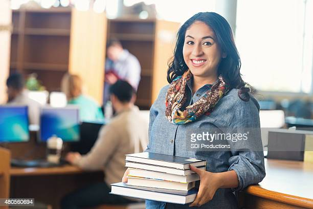 Young adult college student borrowing books from library