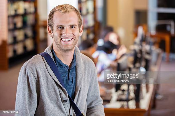 Adulto joven estudiante en la biblioteca Universidad sonriendo Laboratorio de computación