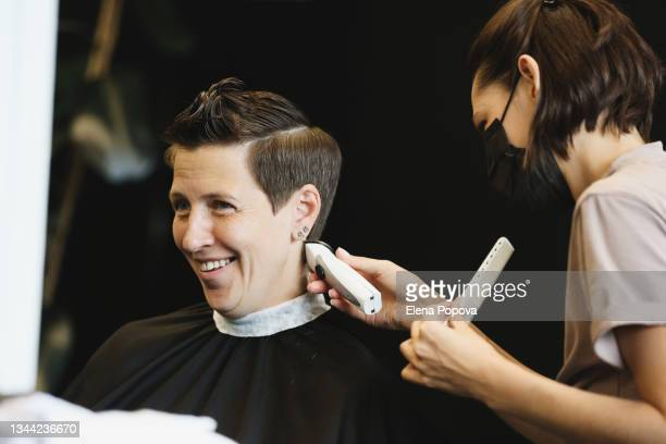 young adult confidence woman getting new haircut at the salon - ambient light stock pictures, royalty-free photos & images