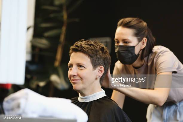 young adult confidence woman getting new haircut - ambient light stock pictures, royalty-free photos & images