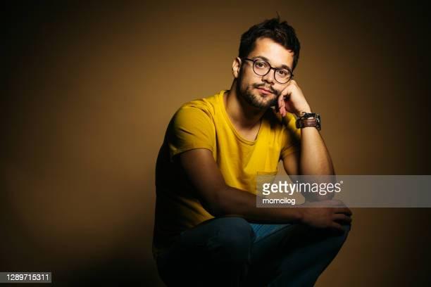 joven adulto seguro de hombre sentado y sonriendo - un solo hombre fotografías e imágenes de stock