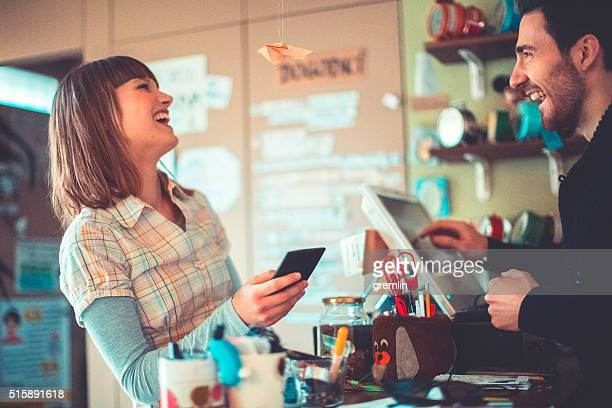 Young adult, contactless payment at the bar counter