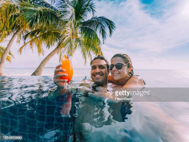 young adult couple doing a selfie in the swimming pool in a paradisiac island - vacanze foto e immagini stock