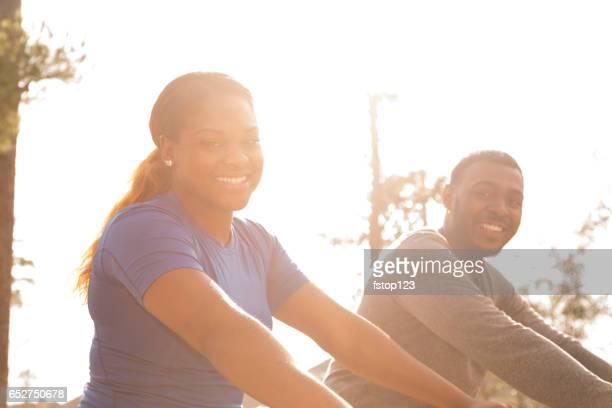 Young adult couple enjoy biking in neighborhood park.