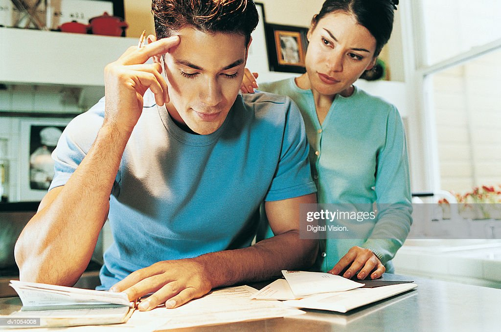 Young Adult Couple in a Kitchen, Woman Supporting Man, Man Anxious : Stock Photo
