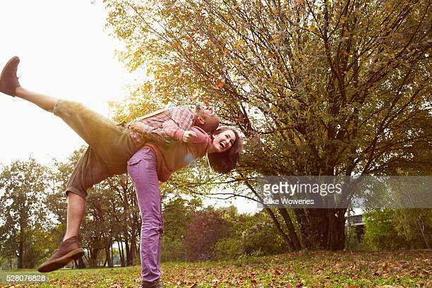 young adult couple in love playing around in a park on a autumn's day, backlit.