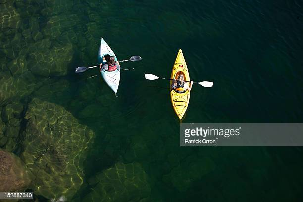 A young adult couple kayaking on a sunny day on a lake in Idaho.