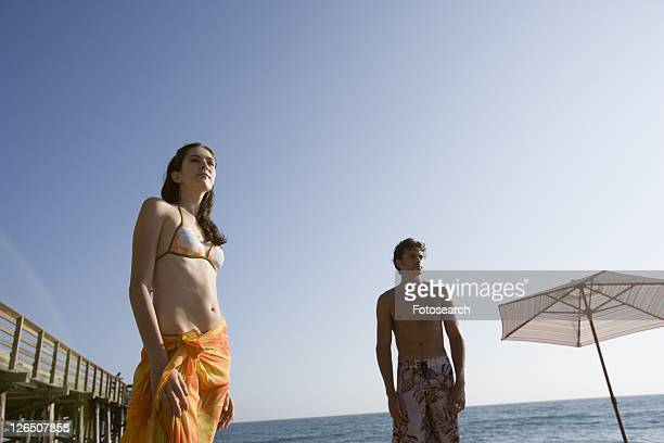Young adult couple looking away on beach, Low Angle View, Copy Space
