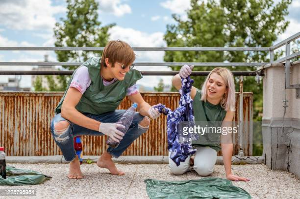 young adult couple making tie dye clothes outdoors on the rooftop - tie dye stock pictures, royalty-free photos & images