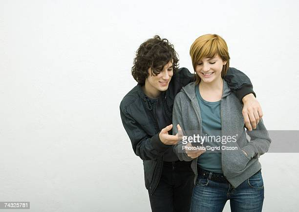 Young adult couple, man with arm around woman, woman holding cell phone