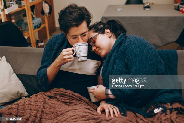young adult couple sharing a cozy night in together at home with hot drinks - ナイトイン ストックフォトと画像