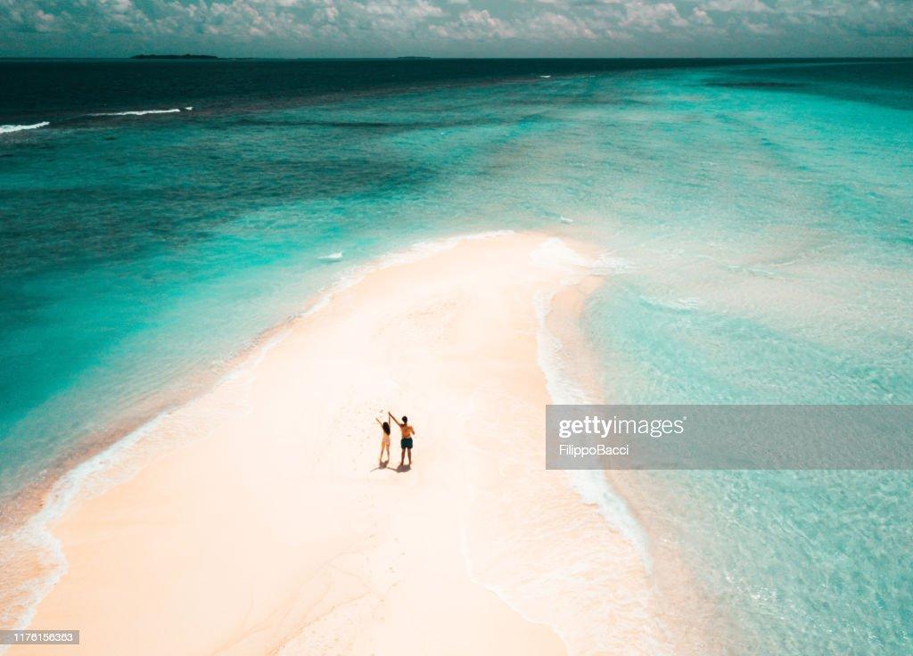 Jeunes couples adultes restant sur un banc de sable contre l'eau turquoise aux Maldives : Photo