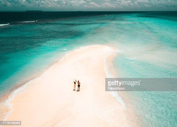 jeunes couples adultes restant sur un banc de sable contre l'eau turquoise aux maldives - idyllic photos et images de collection