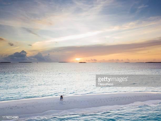 jeunes couples adultes restant sur un banc de sable aux maldives au coucher du soleil - lagon photos et images de collection