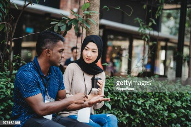 young adult couple taking a break from business during an event - stuart florida stock pictures, royalty-free photos & images