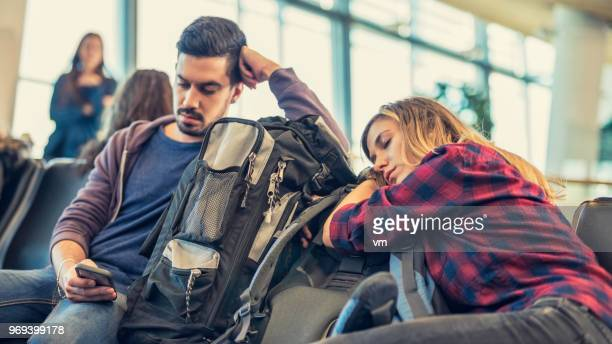 young adult couple waiting at an airport lobby - commercial aircraft stock photos and pictures
