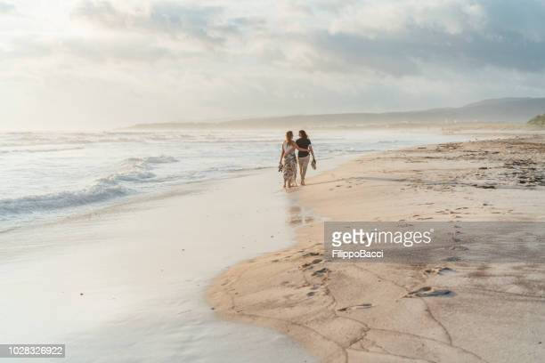 young adult couple walking on the beach together - civil partnership stock pictures, royalty-free photos & images