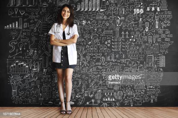 young adult doctor drawing plans on blackboard - blackboard visual aid stock pictures, royalty-free photos & images