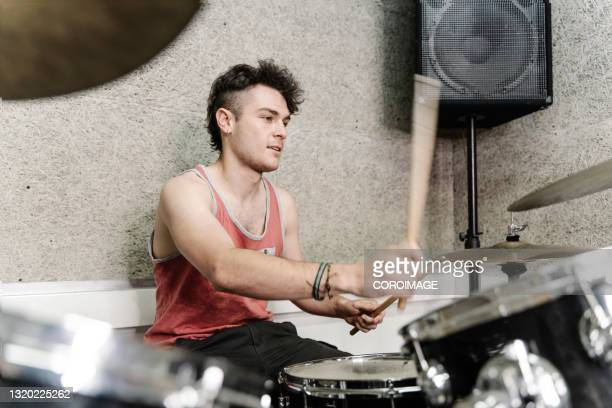 young adult drummer in tank top playing the drums in studio - early rock & roll stock pictures, royalty-free photos & images