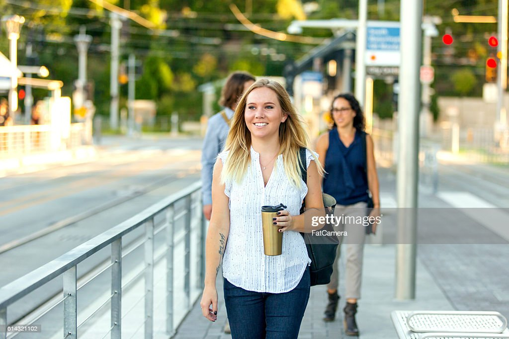 Young adult female at a public transit station drinking coffee : Stock Photo