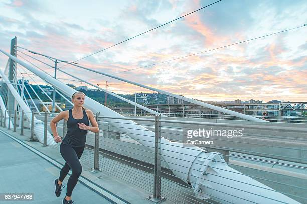 Young adult female athlete running next to public transit