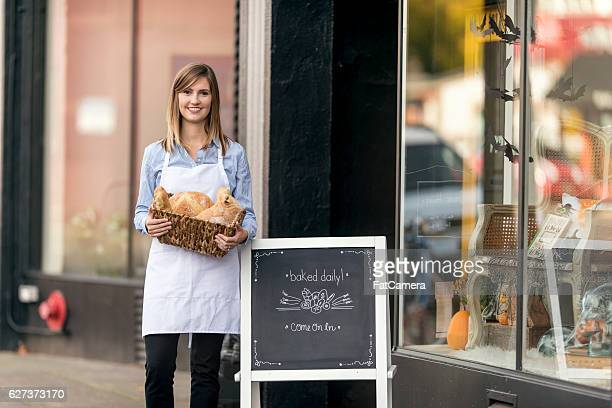 Young adult female business owner standing out front with goods