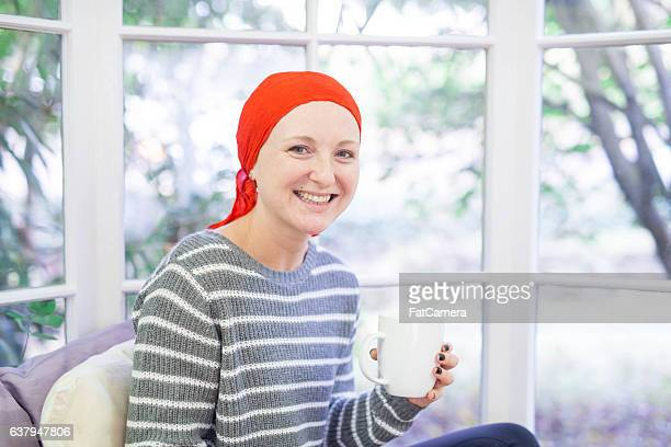 A young adult female cancer patient is sipping tea