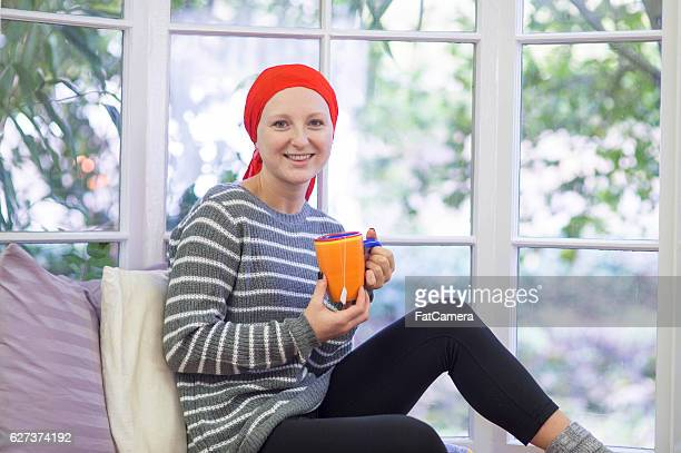 Young adult female cancer patient sipping tea at home