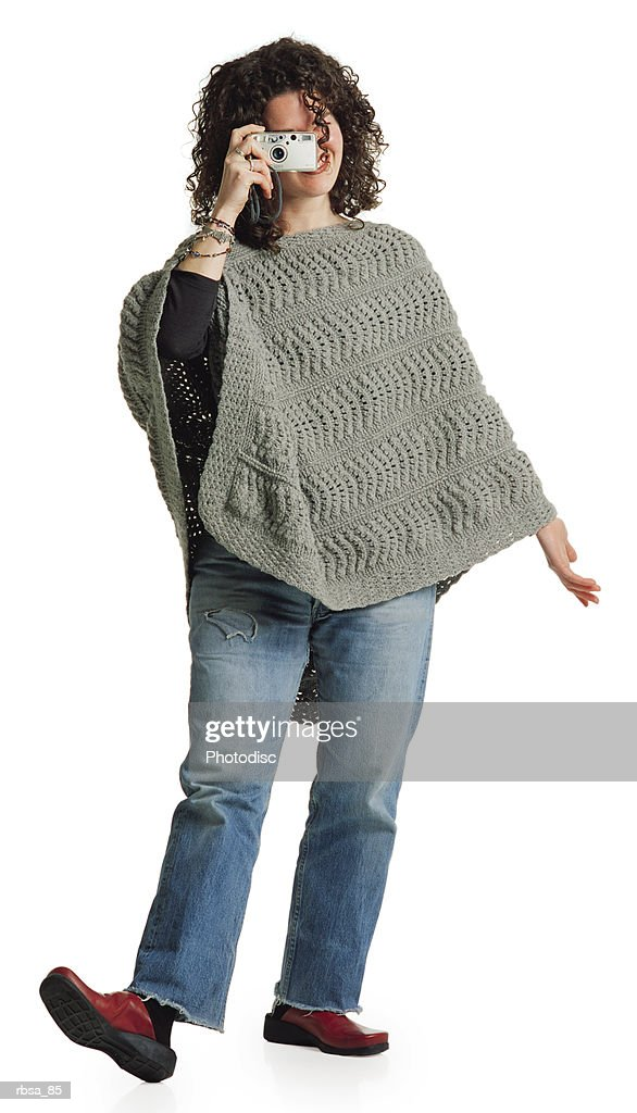 young adult female caucasian with long curly brunette hair wearing old jeans and a gray knit poncho stands with her right toes pointing upward as she holds a camera to her eye and aims looking forward : Foto de stock