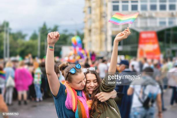 young adult female couple  at pride parade - lgbtqi pride event stock pictures, royalty-free photos & images