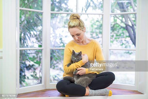 Young adult female craddling her cat in a reading nook