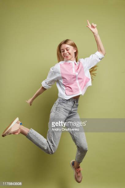 young adult female jumping for joy - jumping stock pictures, royalty-free photos & images