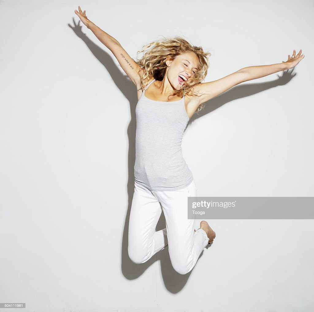 Young adult female jumping for joy : Stock-Foto
