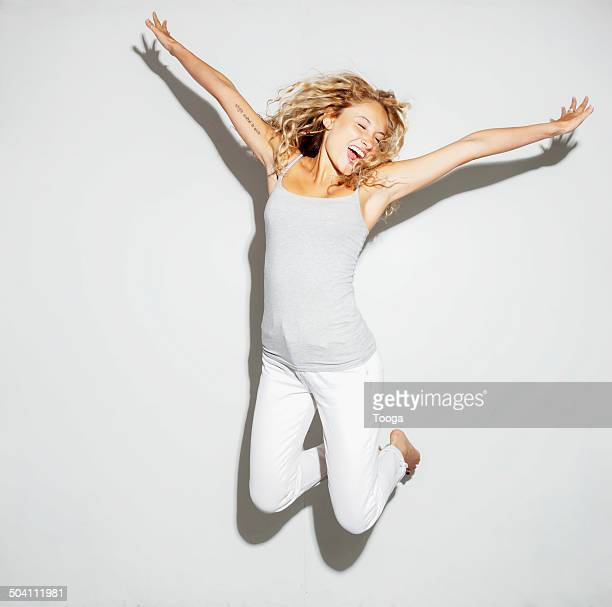 young adult female jumping for joy - white pants stock pictures, royalty-free photos & images