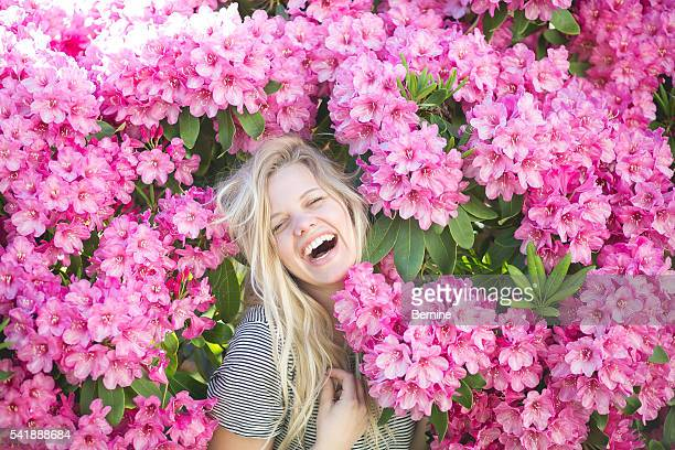 Young Adult Female Laughing Among Flower Bush