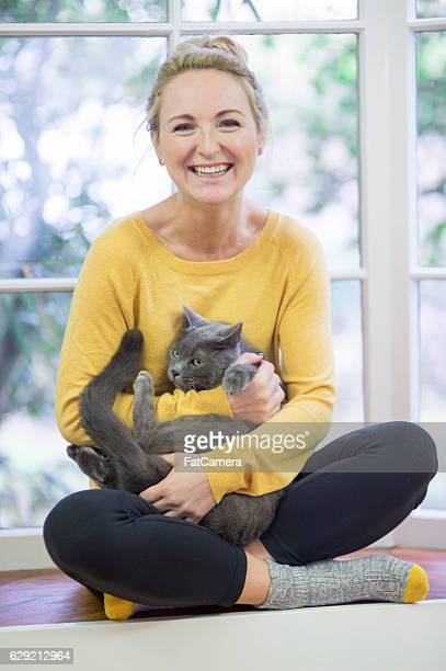Young adult female smiling while cradling her grey house cat