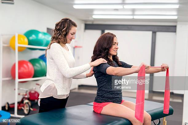 Young adult female therapist massaging an adult females shoulder