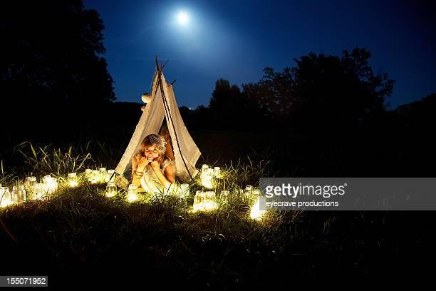 Jeune adulte femme sous le clair de lune dans la tente