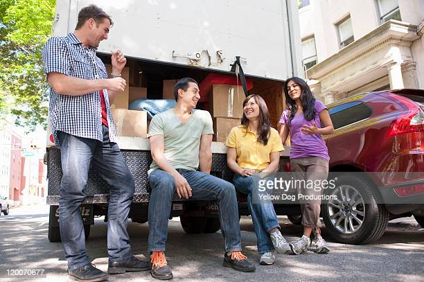 Young Adult Friends at the  back of moving truck
