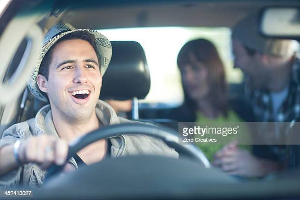 Young adult friends driving in car