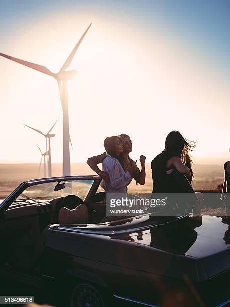 Jeune adulte amis enjoing temps ensemble avec guitare au coucher de soleil
