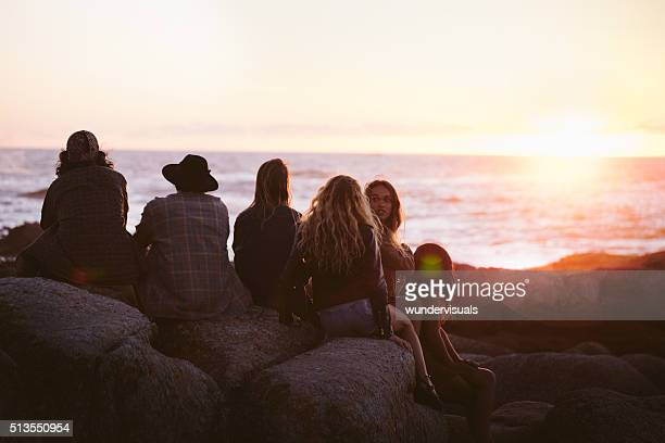 Young adult friends enjoying a sunset at the sea