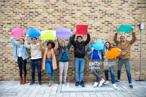 young adult friends holding up copy space placard thought bubbles - international match stock pictures, royalty-free photos & images