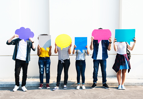 Young adult friends holding up copy space placard thought bubbles 945423310