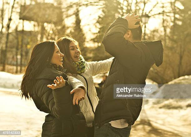 Young adult friends meeting in park in winter
